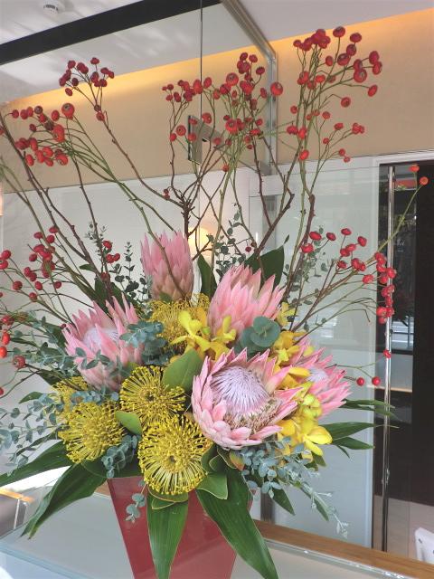 キングプロテア、ピンクッション、バラの実などのアレンジメント